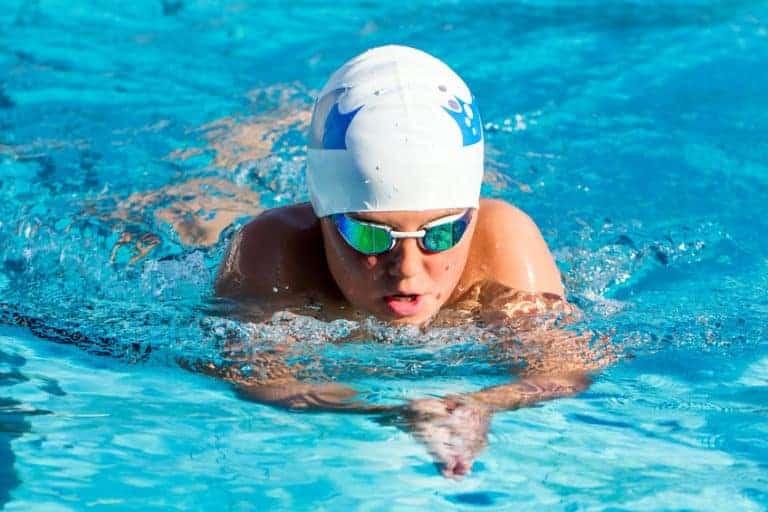 Imagem de nadador em piscina com touca e óculos de natação.