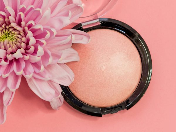 Powder or highlighter in a round package on a pink background with a flower. Beauty and cosmetics, concept
