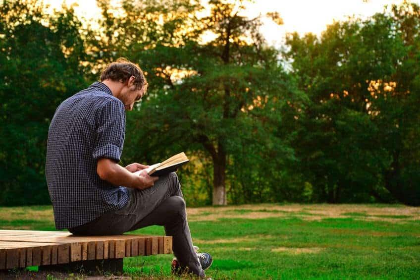 Homem sentado lendo.