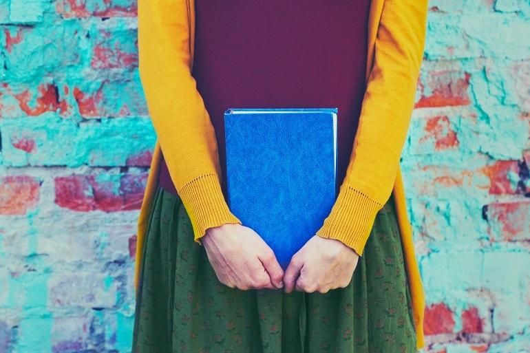Imagem de mulher segurando livro azul.