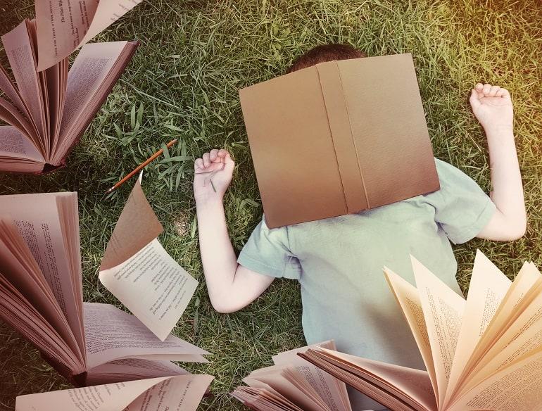 Imagem de homem deitado e livros voando sobre ele.