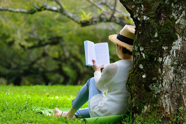 Imagem de mulher encostada em árvore lendo livro.