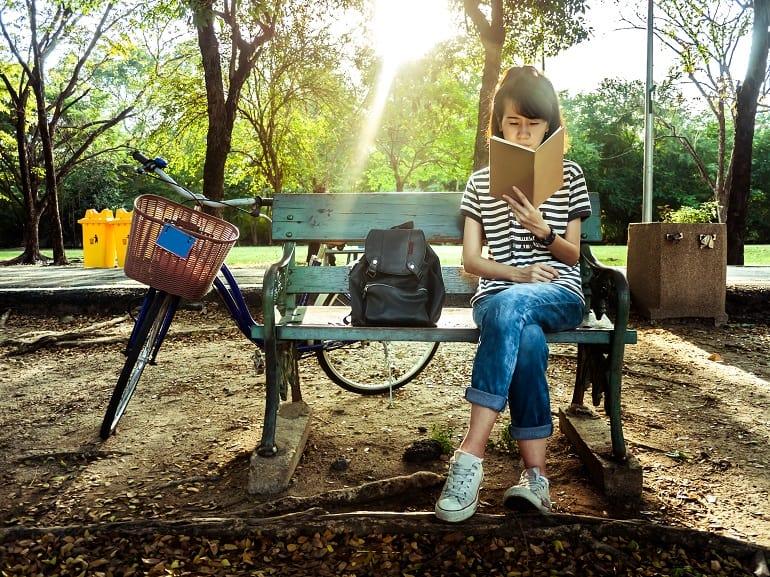 Mulher lendo livro sentada em banco de praça.