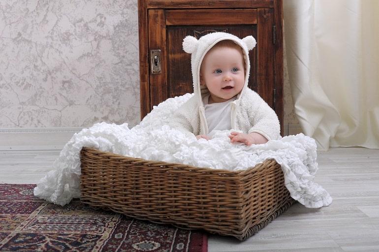 Bebê em moisés com coberta branca.