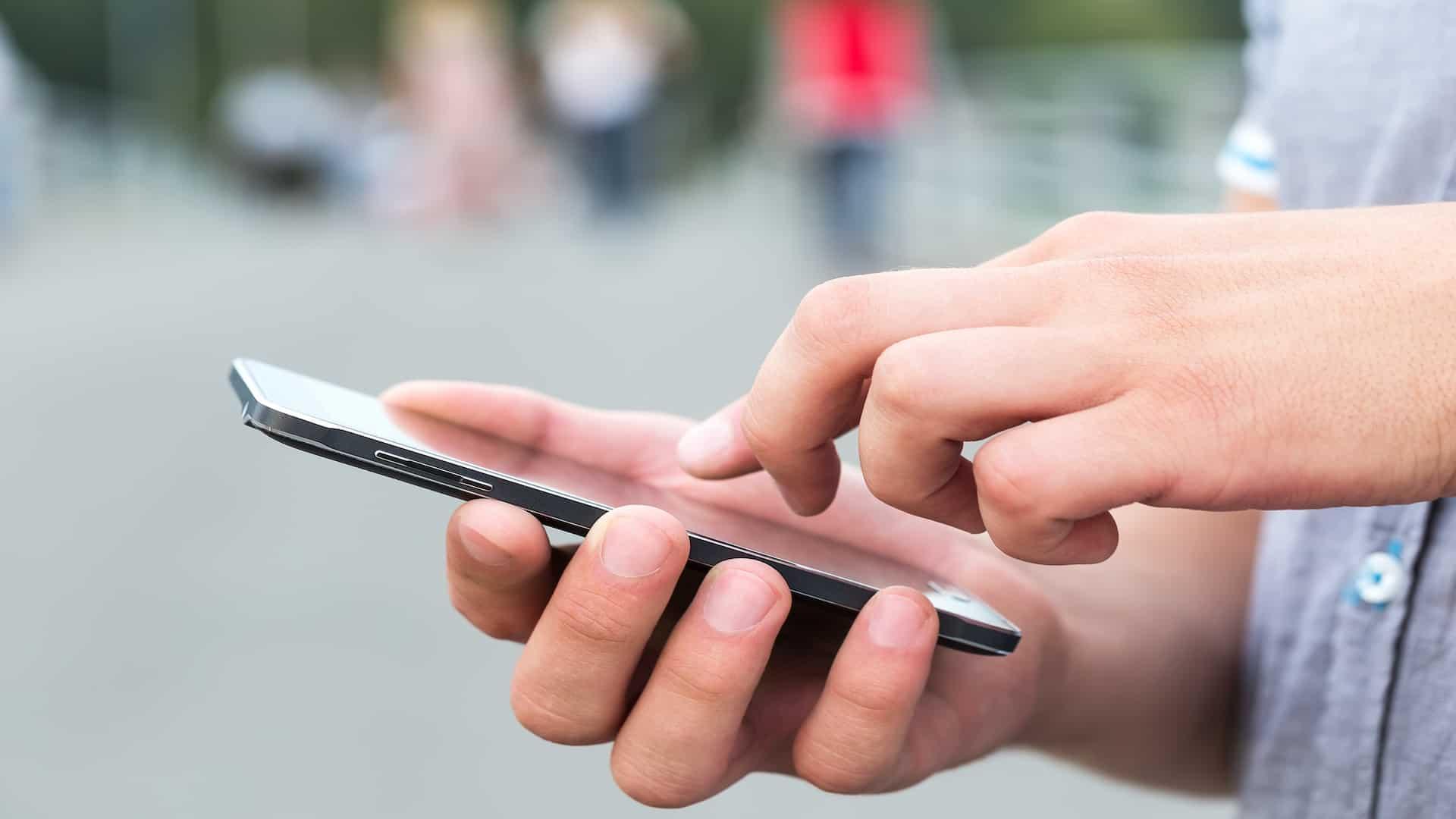 Imagem de pessoa com celular Samsung na mão.
