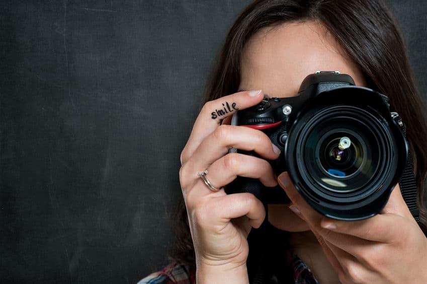 Mulher fotografando com câmera nikon.