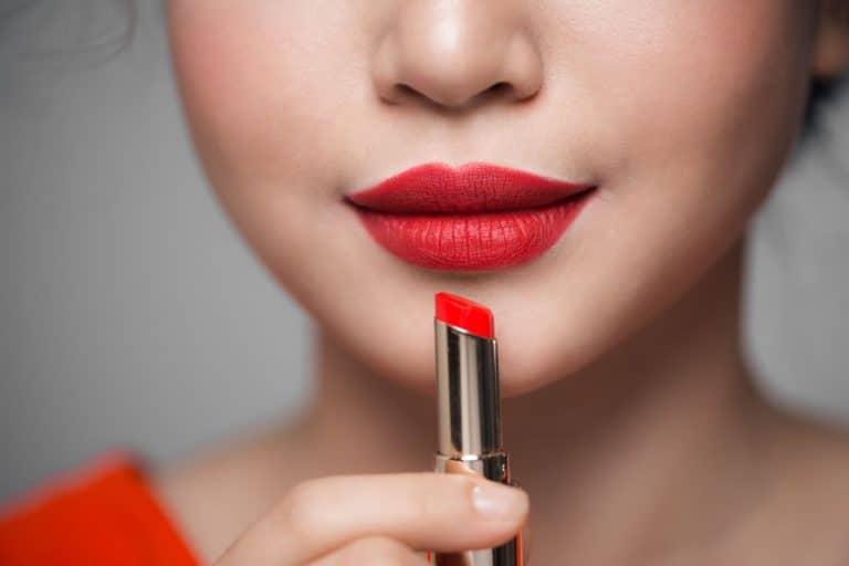 Imagem mostra uma mulher com os lábios pintados de vermelho e um batom na mão.