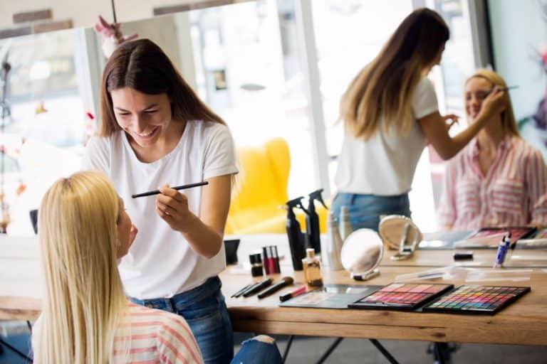 Imagem de mulher maquiando outra.