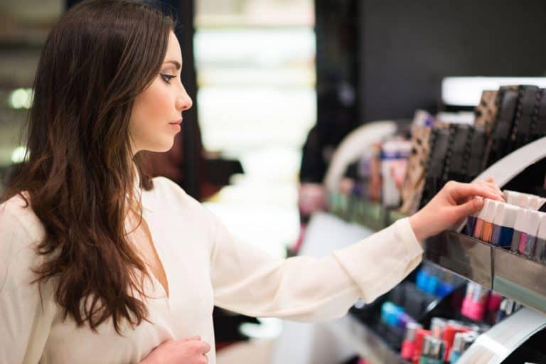 Mulher escolhendo maquiagens em loja.