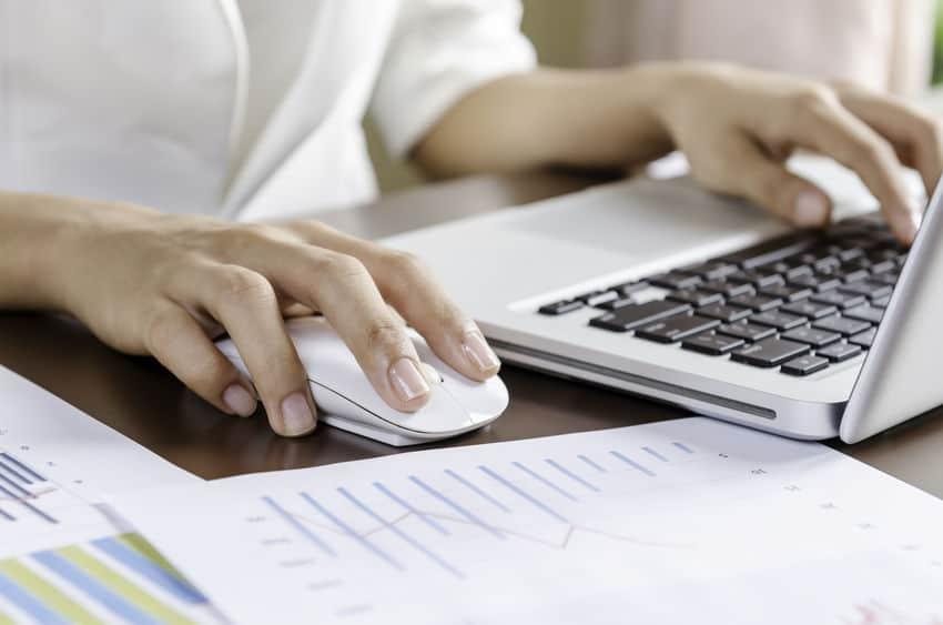 Imagem de pessoa trabalhando com computador e usando mouse sem fio.