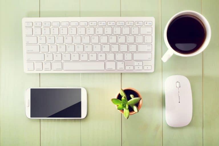 Teclado, mouse, café, smartphone e planta sobre mesa.