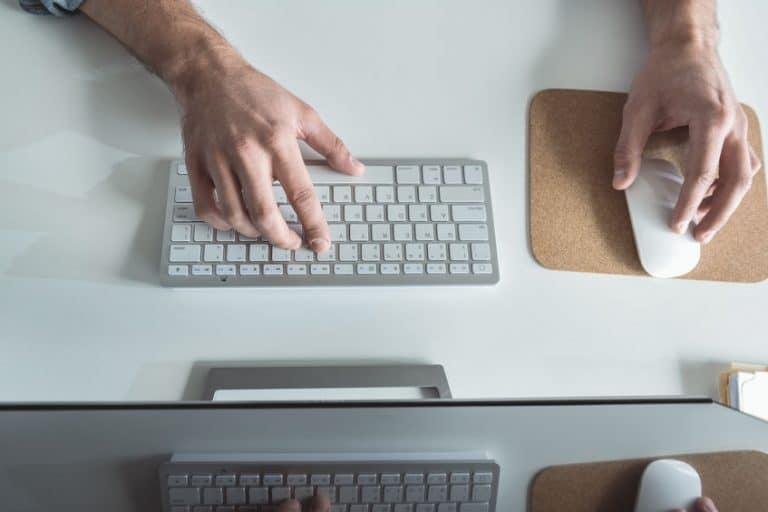 Pessoa digitando em teclado.