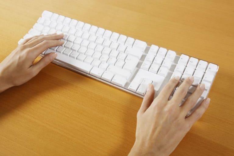 Pessoa digitando em teclado sem fio.