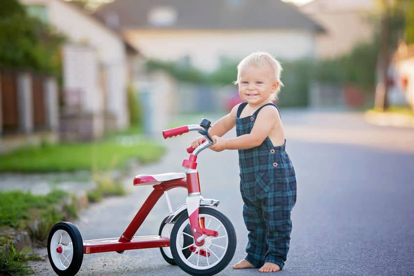 Criança com triciclo vermelho.