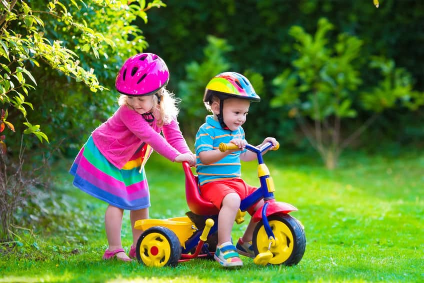 Crianças brincando com triciclo.