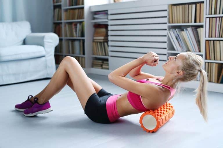 Imagem de mulher fazendo abdominal com rolo de espuma.