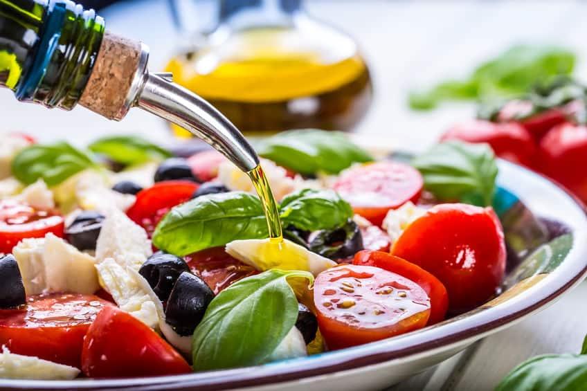 Temperando salada com azeite de oliva.