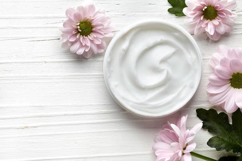 Imagem de pote de creme cheio com flores em volta.