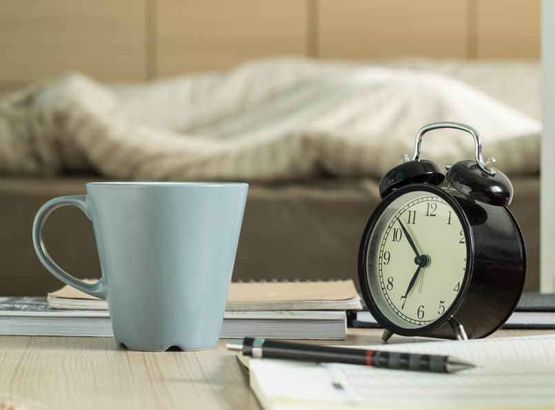 Imagem de despertador sobre mesa em quarto.