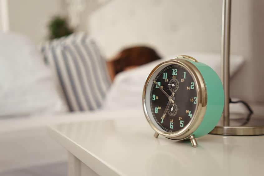Imagem de despertador verde em quarto.