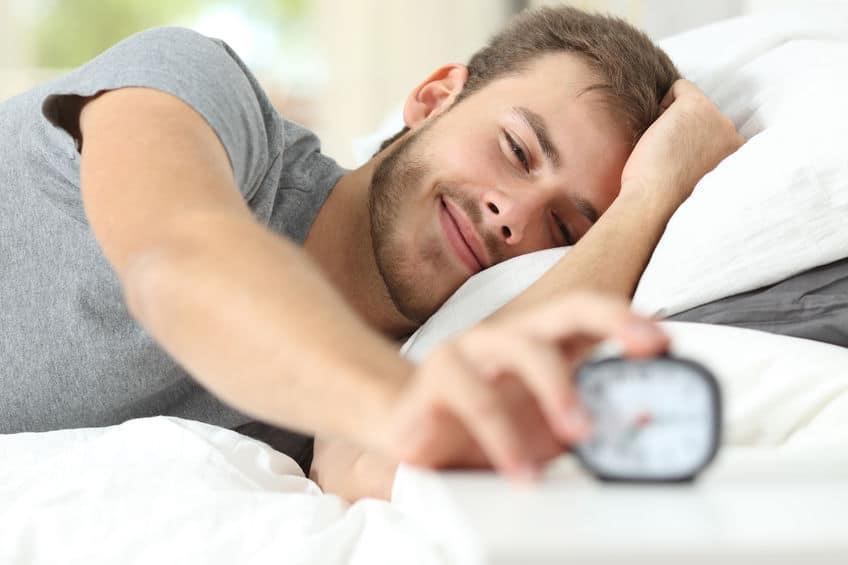 Imagem de homem deitado em cama acordando, desligando o despertador.
