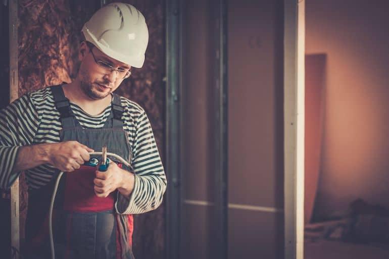 Homem com capacete de segurança utilizando alicate para cortar fio.
