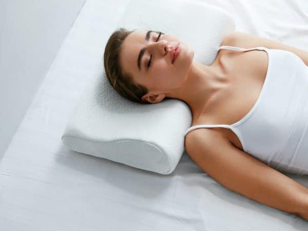 Mulher dormindo em travesseiro cervical.