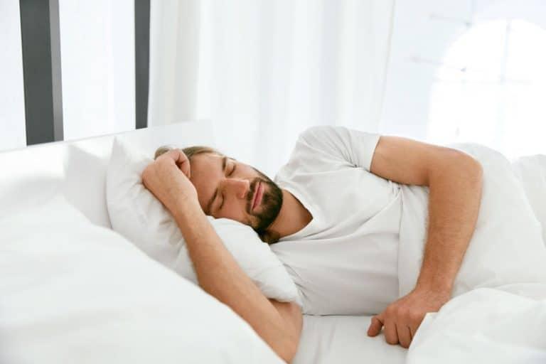 Homem na cama dormindo.