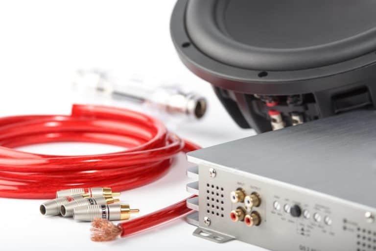 Imagem de cabos e caixa de som próxima a amplificadora de som.