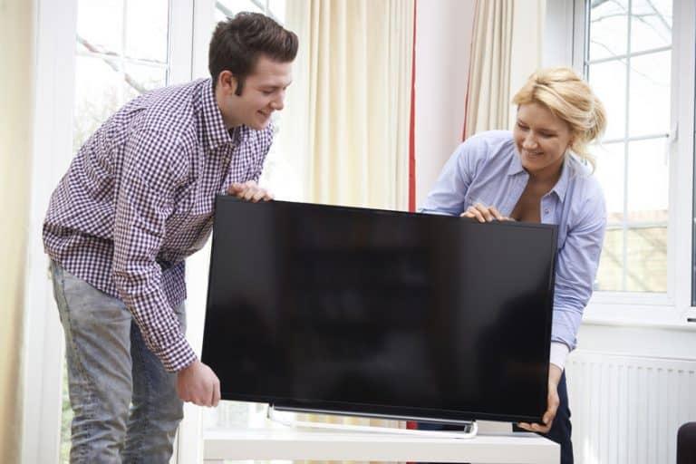 Imagem de casal carregando TV.