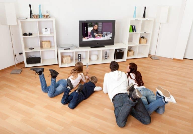 Imagem de família em frente a TV, que está sobre um móvel branco.