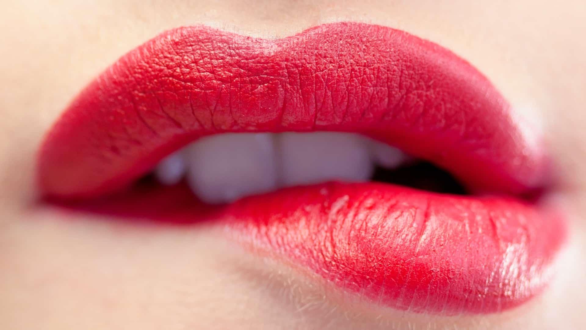 Imagem de boca feminina com batom vermelho mordendo lábio.