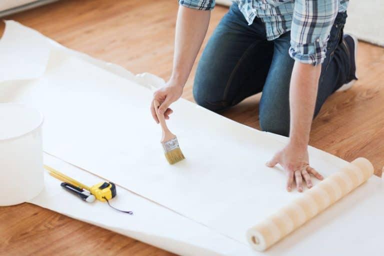Aplicando cola em papel de parede.