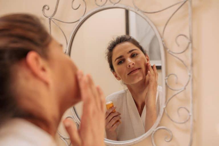 Mulher passando produto no rosto.