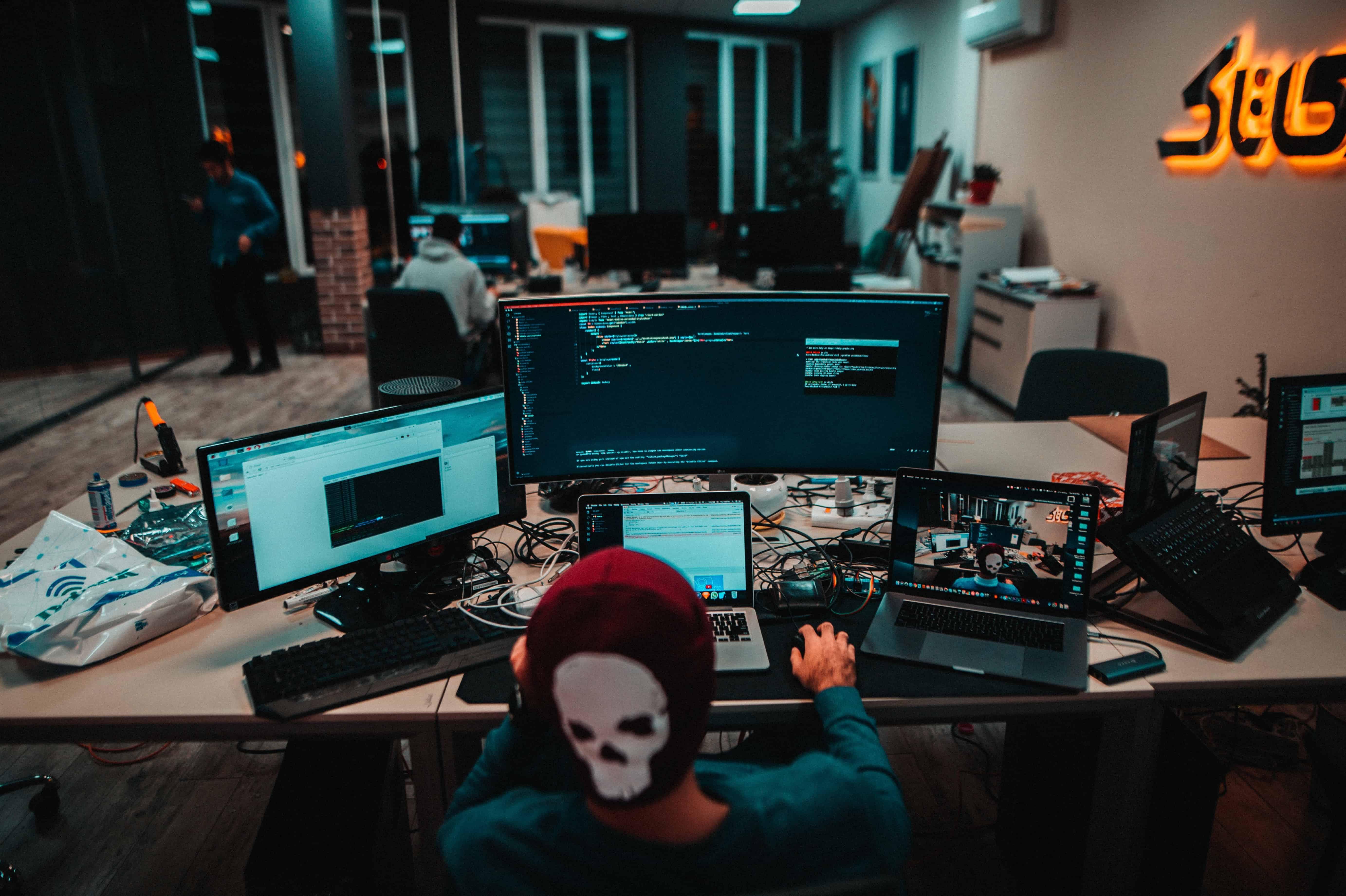 Imagem de pessoa em mesa com diversos monitores.