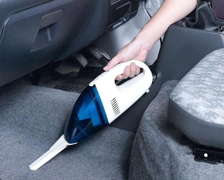 Aspirador de mão sendo passado no carro