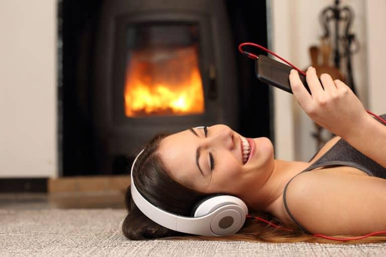 Mulher deitada no tapete ao lado da lareira com celular na mão e fone nos ouvidos