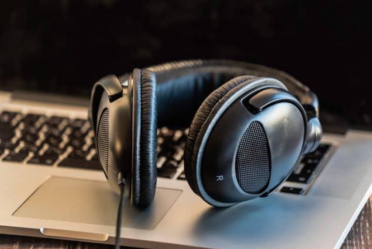 Imagem destaca um fone de ouvido gamer sobre o teclado de um computador