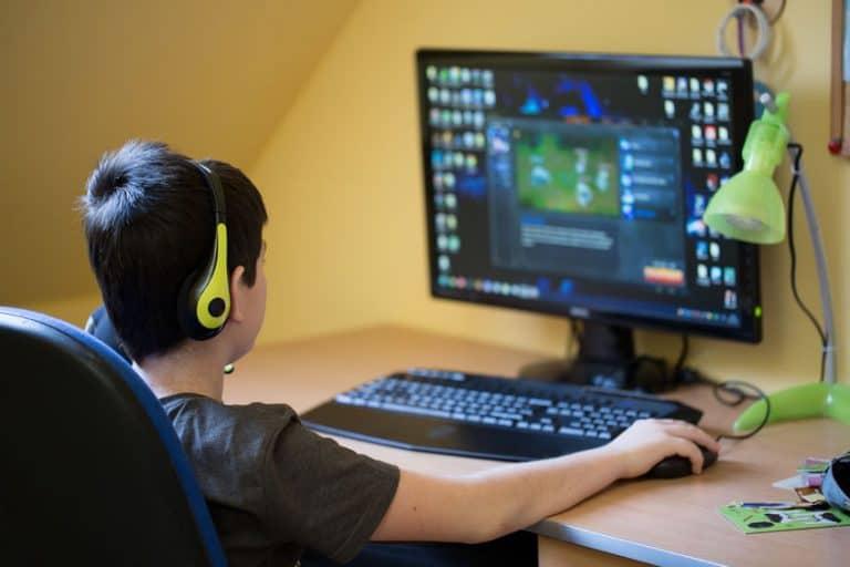Menino joga partida online usando um fone de ouvido gamer