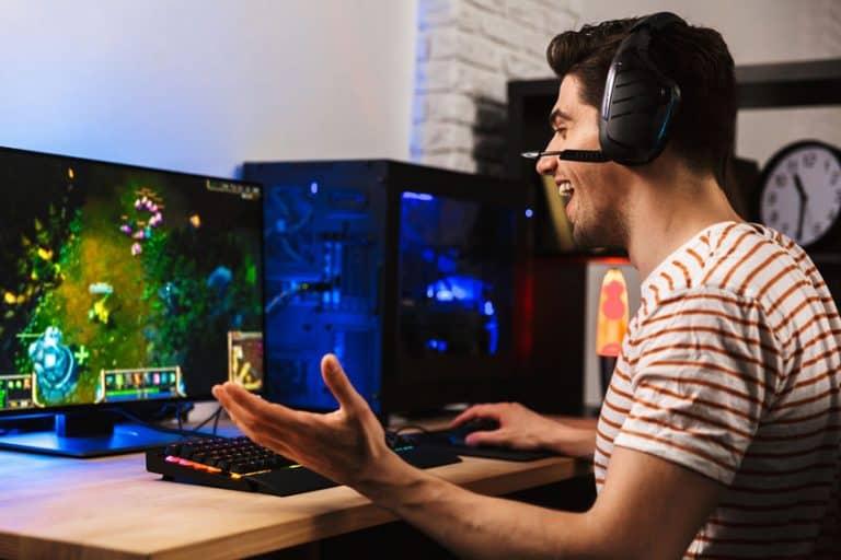 Jovem com fone de ouvido gamer jogando em frente a um monitor de computador