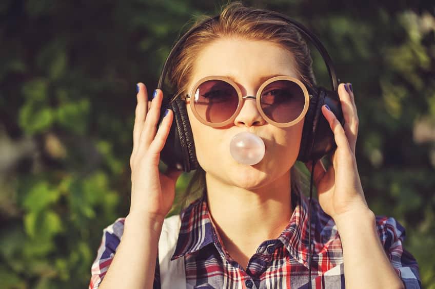 Mulher usando fone de ouvido fazendo uma bola de chicletes