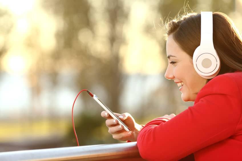 Mulher segura um music player e sorri enquanto ouve música em seu fone de ouvido