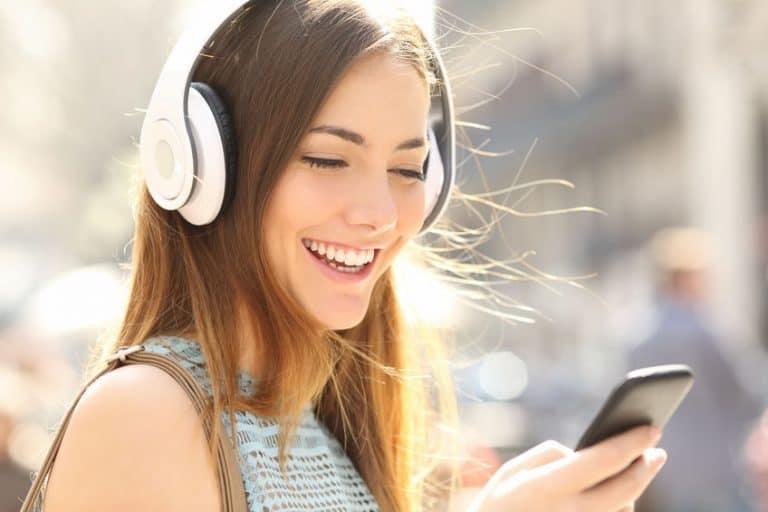 Imagem de mulher com fone de ouvido e mexendo em celular.
