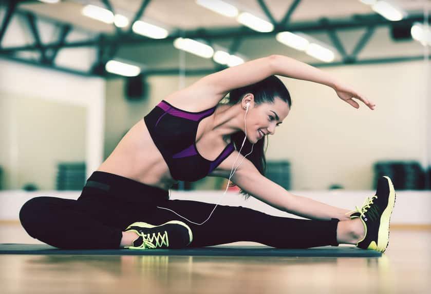 Imagem de mulher fazendo exercício com fone de ouvido.