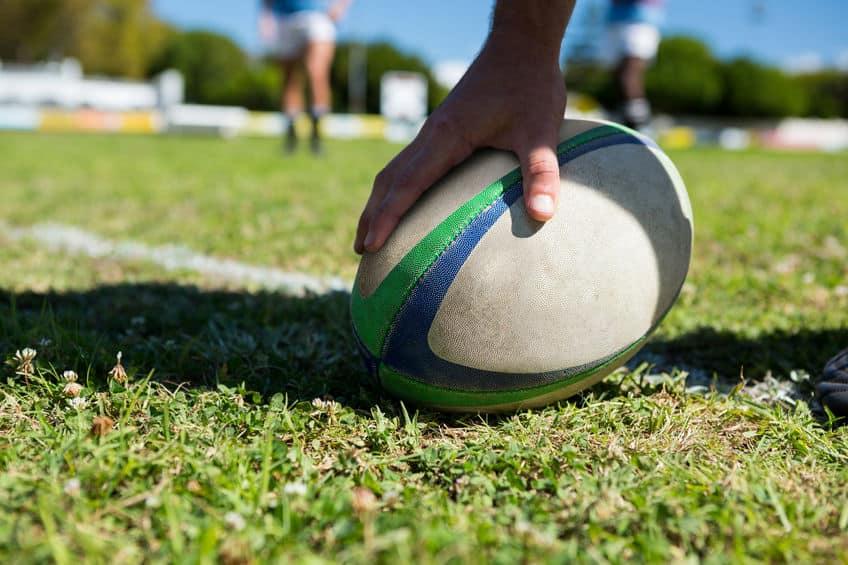 Pessoa segurando bola rugby.