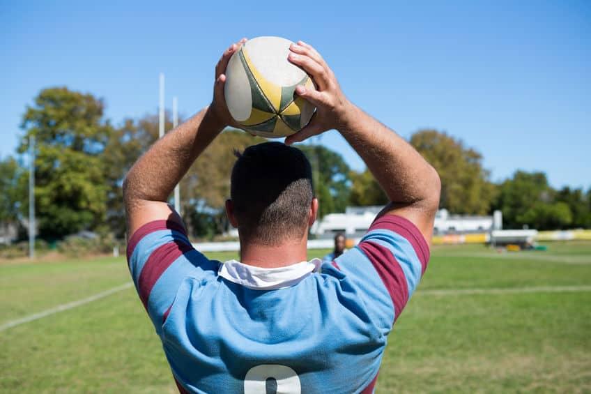 Homem segurando bola de rugby.