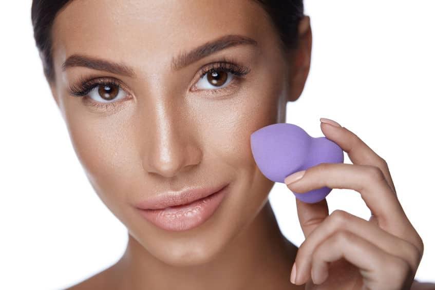 Imagem mostra uma mulher com uma esponja de maquiagem na mão