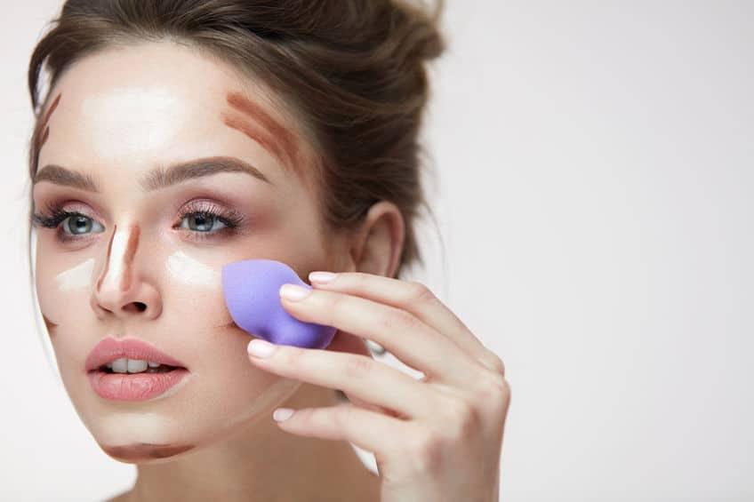 """Imagem mostra uma mulher aplicando a técnica """"contouring"""" com uma esponja Beauty Blender"""