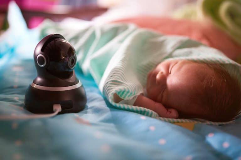 Bebê dormindo com babá eletrônica ao lado.