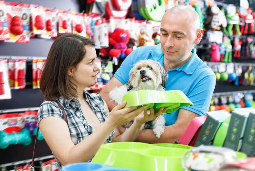 Couple choosing drinking bowl for dog.
